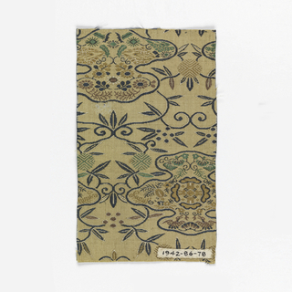 Light tan ground with black vines, geometrically filled ovals, and dotted flowers filling the background.  Amorphous outlined shapes contain various symbols including birds, flowers, plants. Pattern woven in warp floats in black, white, green, bronze, and gold colored threads.