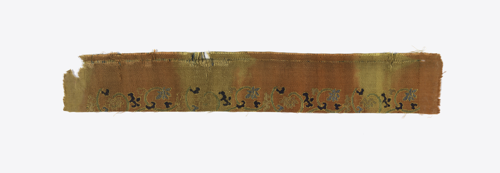 Small fragment with scrolls and flowers in green and blue on an orange and yellow background.