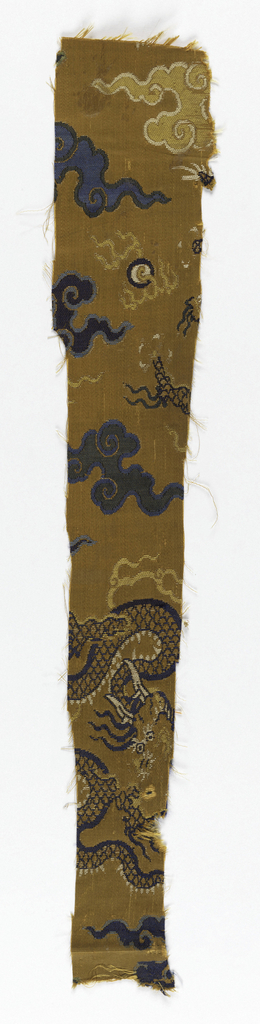 Gold background with pattern of dragons in blue and white silk and metallic wrapped paper threads. Dark and light blue clouds, yellow flames, and blue moons punctuate the background.