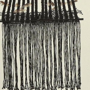 Woven hanging of black linen with a plume of feathers at the top. Woven section first splitting into two parallel strips, then into sixteen narrower strips, before resolving in a wide fringe at bottom. Ornamented with feathers throughout.