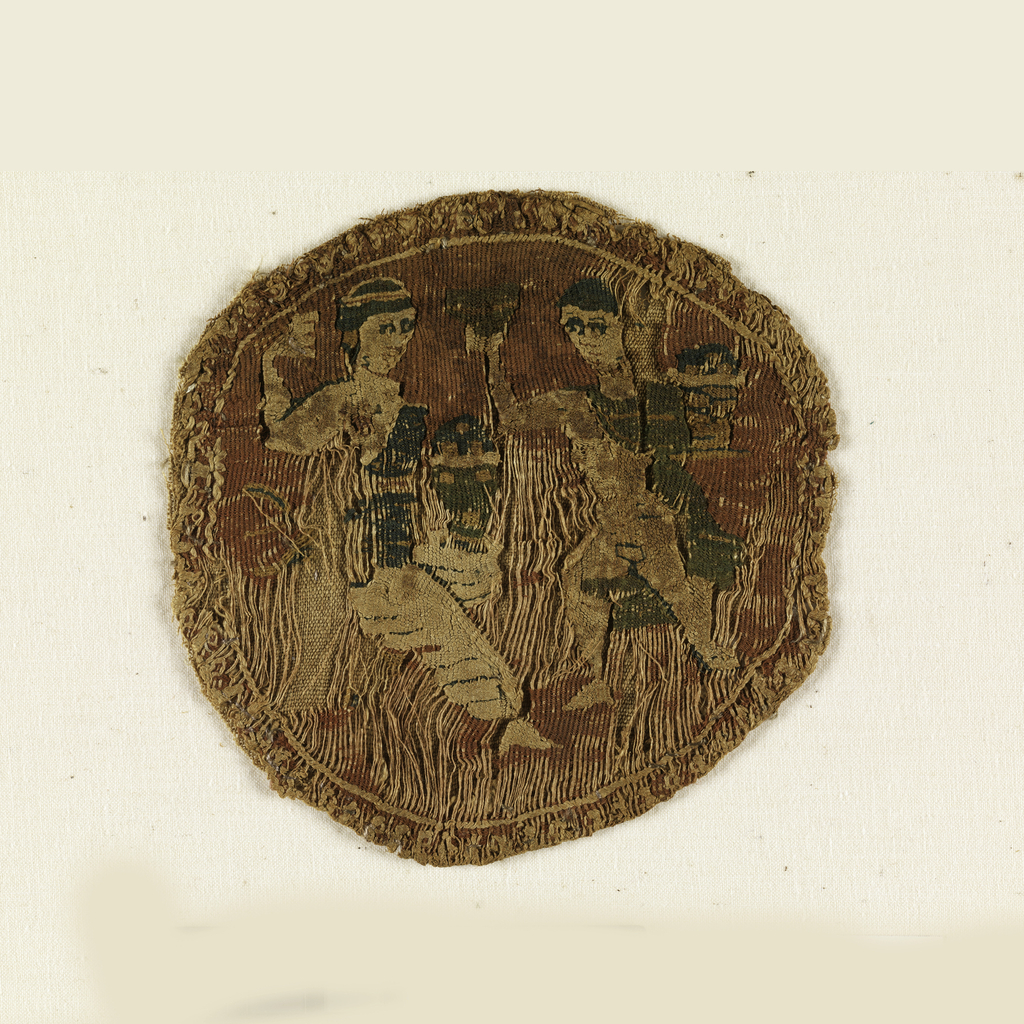 Tapestry medallion depicting a a male and a female figure facing each other. Each appears to be raising a goblet. Figures are woven in white, blue, green and yellow on a red ground.