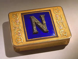 """Box, oblong with rounded corners; gold with bleu de roi enamel plaque on cover with applied """"N"""" inlaid with diamonds."""