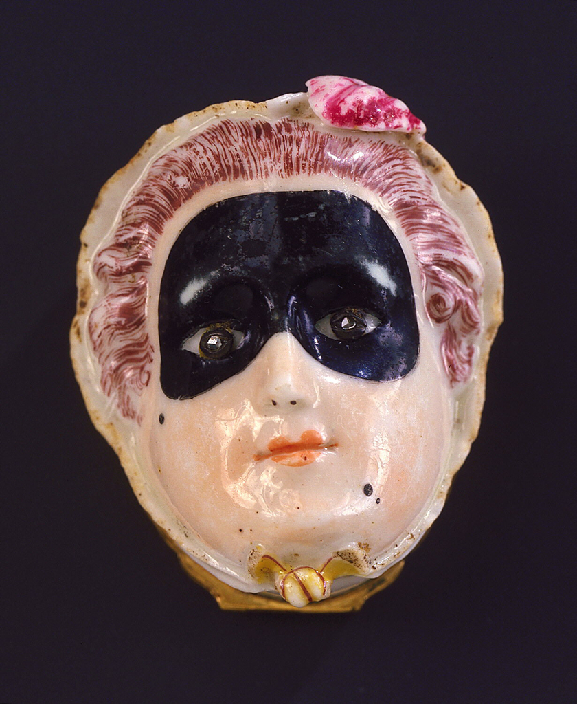 Box in form of woman's head with small 18th-century bonnet and black domino mask; decorated in natural colors in white porcelain; eyes set with rose diamonds; hinged cover of Battersea enamel at back of head, decorated with polychrome flower sprays; gilt metal rims with flame mouldings and twisted gilt wire thumb-piece.