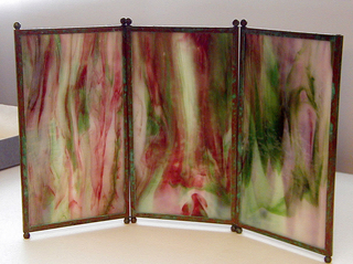 There are three screens. Each consists of three vertically rectangular panels of marbleized glass, each panel framed with narrow copper edging oxidized to green and orange-red tones with two small ball feet at each end. The panels are hinged together by means of wire at juncture of feet and screen.  Glass marbleized in tones of lavender, green and red.