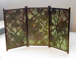 """Three vertically rectangular panels of marbleized glass, each panel framed with narrow copper edging oxidized to green and orange-red tones with two small ball feet at each end. The panels are hinged together by means of wire at juncture of feet and screen. Cut out copper overlay.  Glass marbleized in tones of lavender, blue and green overlaid with cut out copper in """"Grapevine"""" pattern."""