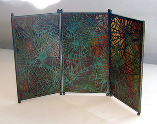 """Three vertically rectangular panels of marbleized glass, each panel framed with narrow copper edging oxidized to green and orange-red tones with two small ball feet at each end. The panels are hinged together by means of wire at juncture of feet and screen. Cut out copper overlay.  Glass marbleized in tones of red, green and amber with cut out overlay in """"Spider web"""" pattern."""
