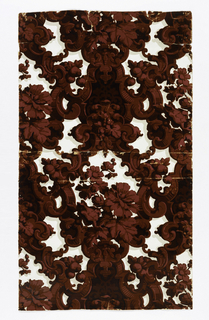 Rococo Revival style: scrolls and medallions forming a diaper pattern, enclosing flowers and foliage. Printed in deep red flock, overprinted with red and black detailing, on a white satin ground with gray shadows.