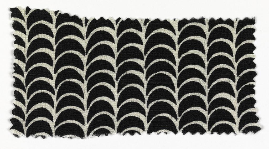 Black ground with white scallop pattern.