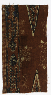 Red field with red and blue vegetation, flowers, and triangles.  Band down selvedge edge with flowers.