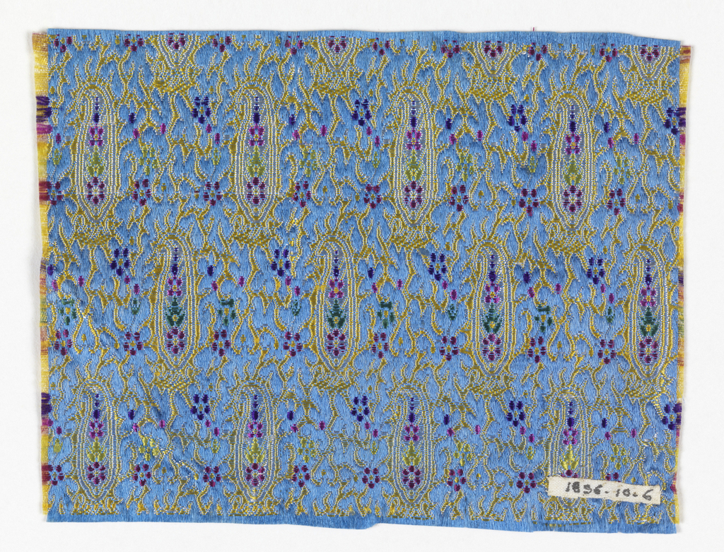 Fragment of woven silk with a yellow paisley pattern on a blue ground. Flowers and details in white, pink, green, red, and purple.