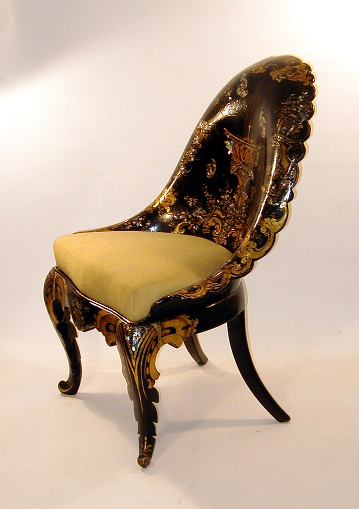 Side chair, with vestigial arms molded in one piece with rounded back having rolled and scalloped edge; cabriole legs; slip seat (upholstered Dec. 1967).  Black ground with gilded rococo-revival designs, mother-of-pearl inlay: central motif- fountain, birds and butterfly.