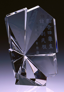 Clear glass sculpture (a), reminiscent of an irregularly faceted block of rock crystal, engraved with a Confucian inscription in formal Chinese calligraphy. Square black wooden base (b); red leather-covered case (c); read leather-covered folder containing black and white photograph and information about the sculpture (d).