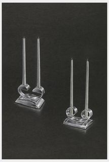 Two designs for double candlestick holders. Both silver rectangular bases with a curved top with C-shaped holder. On the left, the bottom of each holder is flat; on the right, the holders are circular.