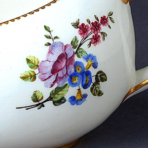 Oval body with vertical handle at higher end; white ground with gilt band of small scallops around rim, gilt band around base and gilding on handle.  Six sprays of multicolored flowers around body.