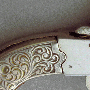 A miniature pistol made in a silver colored metal. The pistol is a plain except for a decorative handle in a scrolled pattern.