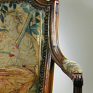The chairs' frames are of carved, unpainted fruitwood.  The chairs' backs, seats, and armpads are upholstered and eged with brass-headed nails.  The chairs' backs are rectangular, wider at the top than at the bottom.  The chairs' top rails are carved in leaf designs on a narrow project-center cornices that groove in concave side curves.  Pyramided acanthus finial surmounts each side rail.  The chair arms terminate in scrolls above curved supports.  The chairs' bowed seat rail rests on  fluted and tapered legs, terminating in plain tapered feet.  The chairs' forelegs are surmounted by cubical blocks.