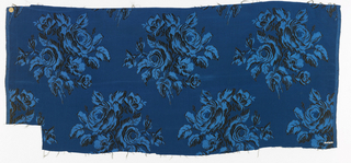 Woven silk textile showing light blue roses on a dark blue ground.