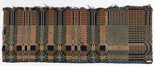 """Fragment of a woven coverlet with a grid pattern and """"pine tree"""" border, in dark blue, pink, and off-white wools."""