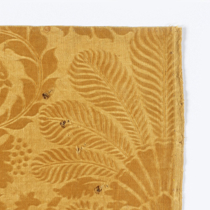 Radiating feather on a field of scrolls. Brownish yellow color.