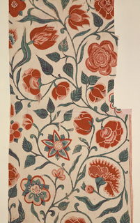 Scrolling vines with red and blue flowers, including tulips and carnations, on a cream-colored ground. Emphasis is given to the forms of the flowers by leaving a very narrow white space between the edge of the petals and the outlines. Piece is seamed across center. Lower section shows evidence of a border at the right side.   White cotton, on which a strongly curved vine appears, from which spring various large flowers.  The foliage is now blue as the yellow has diappeared.  Blossoms in reds, pink: some show details of a gray-violet.  Drawing is heavy, bold, emphatic; flowers seen in profile are realistically drawn; naturalistic veining in leaves.  Emphasis is given the forms of flowers by a trick of leaving a very narrow white space between the edge of petals and the outlines, which are sometimes red, sometimes brown.  Among the flowers the tulip and carnation are identifiable.  Colors: Two shades of red, pink, blue, a gray violet (faded purple), brown and red for outlines.