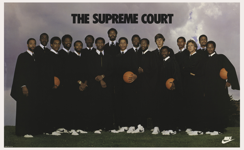 Portrait photograph of the Nike Pro Club group of basketball players all wearing black robes and white Nike sneakers, some holding basketballs. Above, in black: THE SUPREME COURT. Lower right, in white: NIKE [swoosh].