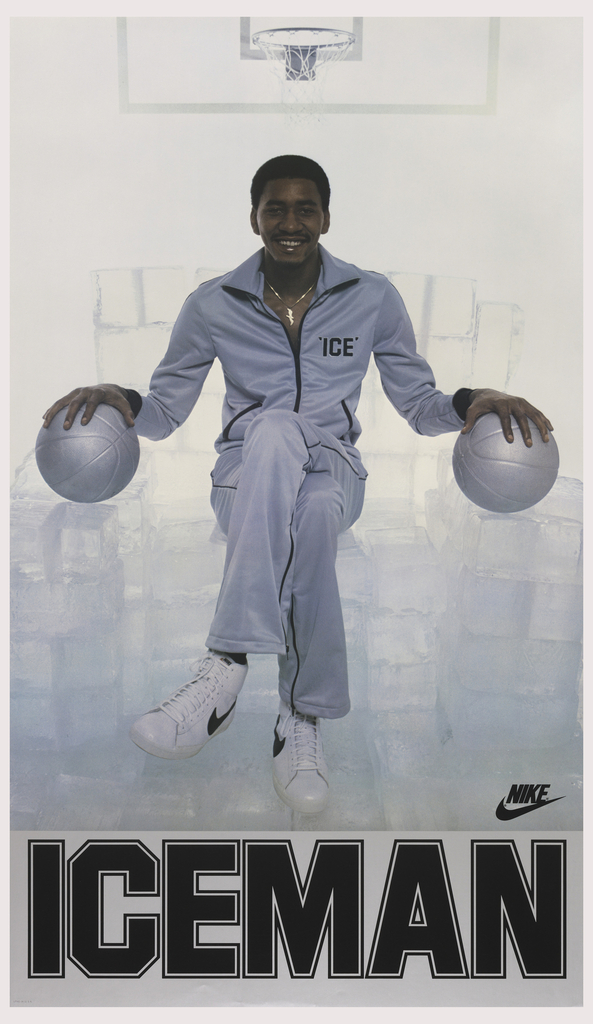 """Photograph of George """"The Iceman"""" Gervin in a space filled with large ice cubes, holding a silver basketball in each hand, wearing a silver tracksuit with the word: 'ICE' embroidered on the chest. He wears white Nike sneakers. In lower margin: ICEMAN; lower left of photograph: NIKE logo."""