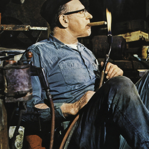 "Photograph of a mechanic in his workroom, lighting a cigar, sitting in a red office chair, leaning back. Room is cluttered. Lower margin, in white ink: ""nelson office seating [logo] herman miller international design group."""