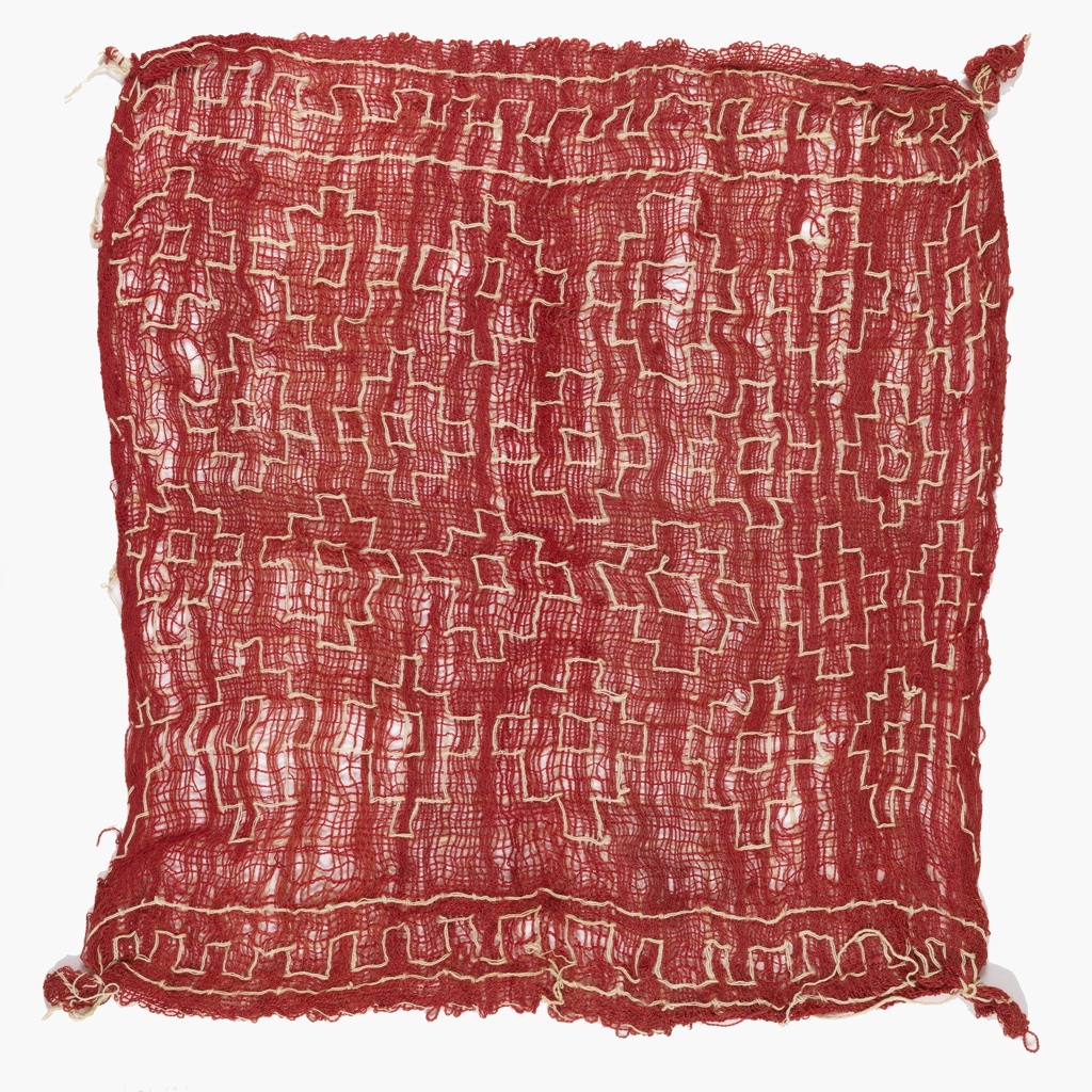 Carrying cloth of loosely woven, overspun wool yarn, in red, possibly dyed with cochineal, with a geometric pattern in white cotton.