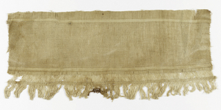 Strip of un-dyed cotton cloth with band containing angular scrolls in cloth weave on twined background; guard strips; cord selvage on one side, to which is hand-sewn fringed border.