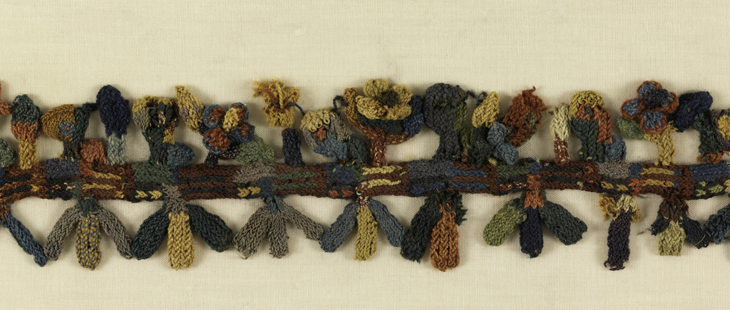 Edging or border of three-dimensional birds and flowers rendered in cross-knit looping.