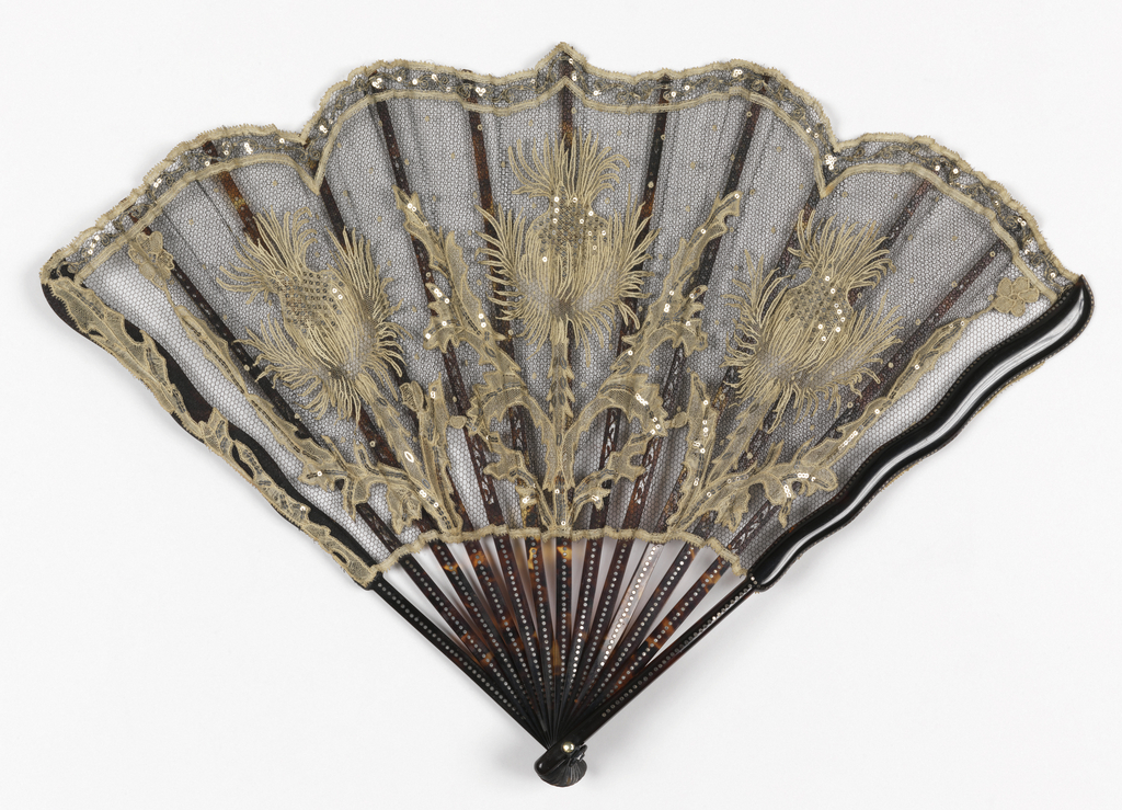 Pleated fan. Leaf of black silk net with three large off-white cotton needle and bobbin lace thistles applied; embroidered with steel spangles. Tortoise shell sticks embedded with steel spangles; tortoise slips. Glass stone at rivet.