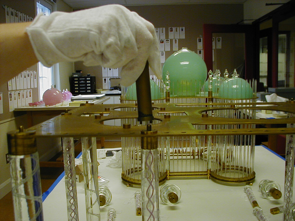 Rectangle constructed of 93 vertical clear glass rods and 10 posts with either white or pink and white internal twists.  Flat gilded brass(?) roof surmounted by a large center dome and four smaller domes, all pink.
