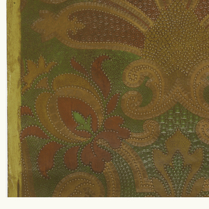 Stylized floral and foliate motif vaguely resembling an anthemion. Printed in deep orange-red and tan against a green background.