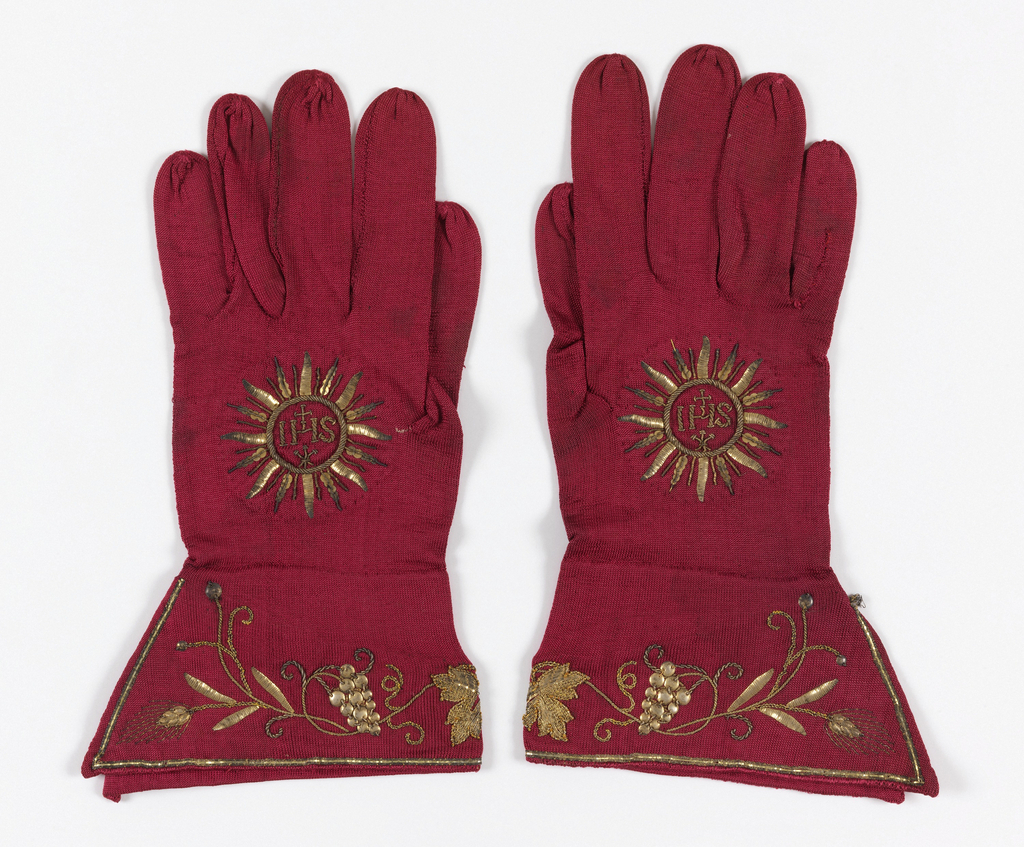"Pair of red Cardinal's gloves with cuffs embroidered in gold metallic yarns and flat gold disks in a vine design with grape clusters. Sacred monogram, IHS, in rayed disk, embroidered in gold on back of each glove. Sewn inside one glove, a handwritten label: ""Cardinal's gloves – real gold embroidery. Bought in Rome, 1897."""