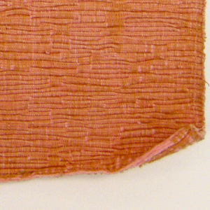Sample of hand woven cotton in which the warps are much thinner and more tightly twisted than the loosely-twisted, slubby wefts. The wefts are grouped in combinations which vary across the width of the fabric, giving a meandering, rather than strictly grid-like, appearance. Ochre warp; pink weft.