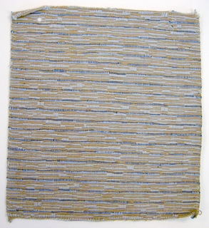 Sample of hand woven cotton in which the warps are much thinner and more tightly twisted than the loosely-twisted, slubby wefts. The wefts are grouped in combinations which vary across the width of the fabric, giving a meandering, rather than strictly grid-like, appearance. Tan and light blue warps; light blue and medium blue wefts.