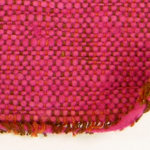 Sample of hand-woven cotton in which the warps are much thinner and more tightly twisted than the loosely-twisted, irregularly spun wefts, which vary in thickness across their length. Burnt orange and brown warps; hot pink wefts.