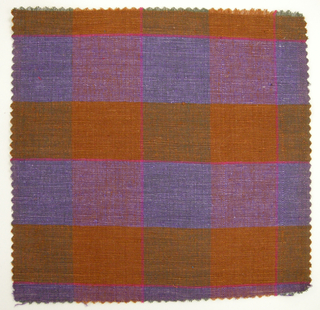 Sample of a hand woven cotton plaid with a slightly slubbed texture.  Warp has wide bands of burnt orange and green; weft has wide bands of burnt orange and purple. With narrow stripes of bright pink in warp and weft directions.
