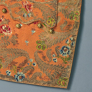 Two waistcoat fronts with a coral-colored foundation with small, all-over floral design. Ornamented at the center front  and lower edges and pockets with gold metallic cornucopias and sprays of polychrome silk flowers. In seven colors of silk and three different metallic yarns.