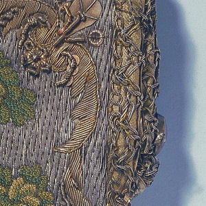 Small shield-shaped purse embroidered in colored silks and metal threads. On one side, a shepherdess and sheep, and on the other a shepherd with a dog, each embroidered in colored silks against a couched silver ground. Figures largely in knot stitch.  Border of gold embroidery with spangles. Clasp of silver or steel, with spring.
