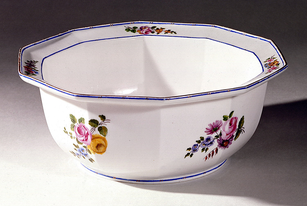 Ten-sided bowl, with flairing rim; white ground decorated with sprays of flowers on exterior and rim; blue bands with touches of gilding along rim and foot.