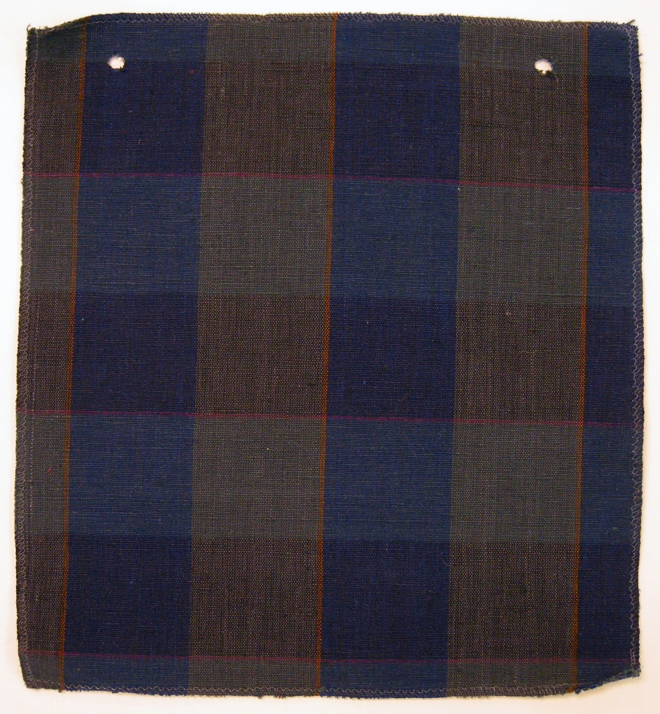 Sample of a hand woven cotton plaid with a slightly slubbed texture. Warp has wide bands of royal blue and slate blue with narrow stripes of burnt orange; weft has wide bands of navy blue and black with narrow stripes of violet.