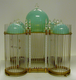 Plan: square center with four turrets; structure composed of numerous glass and brass parts: one large central dome flanked by four small domes on brass roof, all domes of blue-green glass with clear finials; blue-green rectangular panels in-set between domes;  the brass roof and base secured to large clear and white laticino rods by means of brass and glass finials at the top and brass washers at the bottom; walls composed of thin glass rods inserted in brass roof plate and base plates. Removeable glass and brass swings. Square plexiglass undertray.