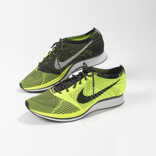 Pair of running shoes with knitted upper with varied textures in flourescent yellow-green and black.
