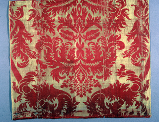 Large scale symmetrical pattern of red leaves on gold background.