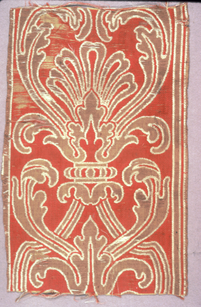 Fragment of a border with a symmetrical design of acanthus leaf and scrolsl in green and white on a red ground.