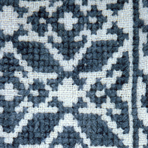 Geometric designs forming an all-over pattern. In blue on a white ground. Border design of tiny trees.