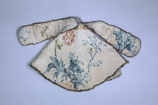 Cape for ecclesiastical figurine, made of a fabric that is patterned with the figure  of a man in Chinese costume sitting on rocks under a tree playing a flute.