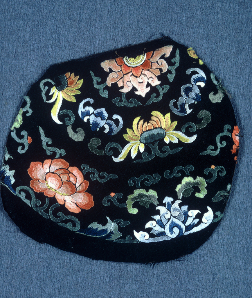roughly circular fragment of dark blue satin embroidered with polychrome silk in design of cloud motif, leaves, lotus, bats etc. with central circular flower. incomplete design cut from larger pieces.