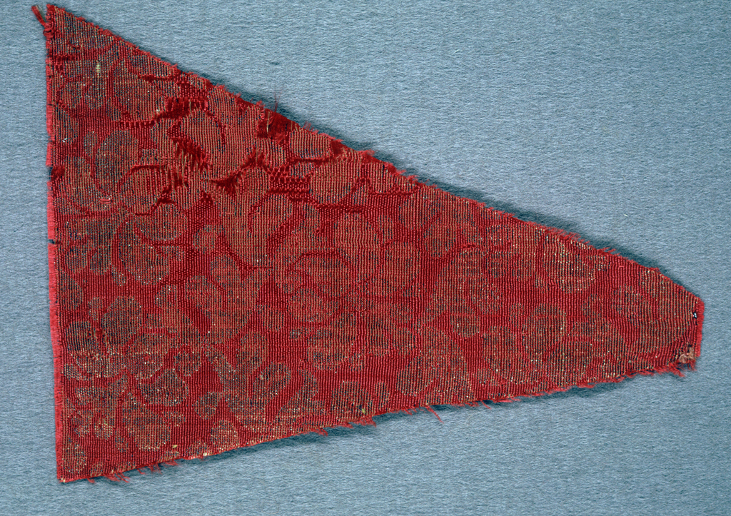 Red ground with design on gold of an open flower and leaf.